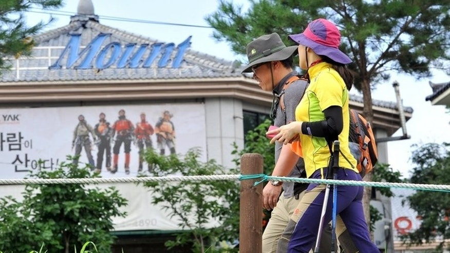 This picture taken on August 3, 2013 shows South Korean climbers walking past a shop selling stand-out designer gear at a trailhead of Mount Bukhansan in Goyang, north of Seoul. Hiking is a national pastime in South Korea and many South Koreans have a near-obsession with latest brand-name outdoor gear.