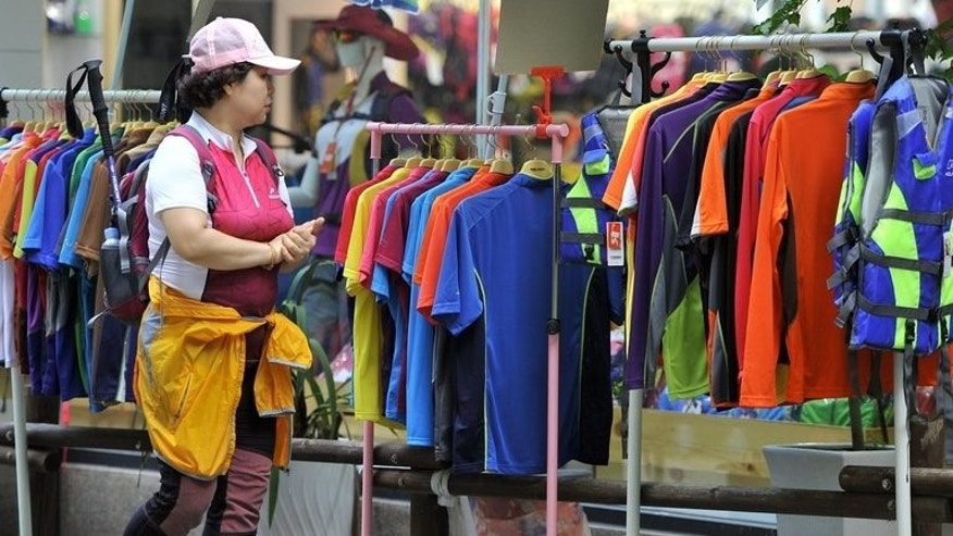A South Korean climber walks past a shop selling designer gear at a trailhead of Mount Bukhansan in Goyang, north of Seoul August 3, 2013. Hiking is a national pastime in South Korea and many South Koreans have a near-obsession with latest brand-name outdoor gear.