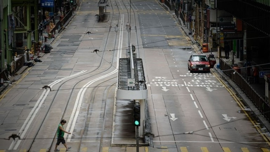 A man crosses an empty street in Hong Kong on August 14, 2013. Hong Kong battened down Wednesday as Severe Typhoon Utor forced the closure of the city's financial market and disrupted hundreds of flights, after leaving six dead in the Philippines.