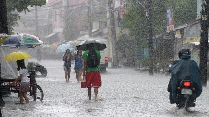 Residents wade through water as heavy rains brought on by Typhoon Utor hit Manila on August 12, 2013. The Philippine's National Disaster Risk Reduction and Management Council said the death toll from the typhoon had risen to six, with five people still missing.