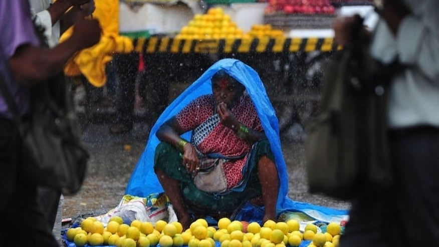 A fruit seller waits for customers during heavy rains in Mumbai on August 13, 2013. India's inflation accelerated sharply to close to six percent in July as a weak rupee pushed up import costs, data showed Wednesday, deepening worries about the slowing economy.