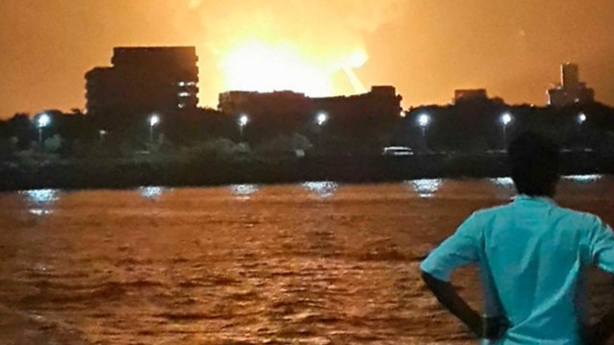 Aug. 13, 2013: A man watches Indian Navy submarine INS Sindhurakshak on fire in Mumbai.
