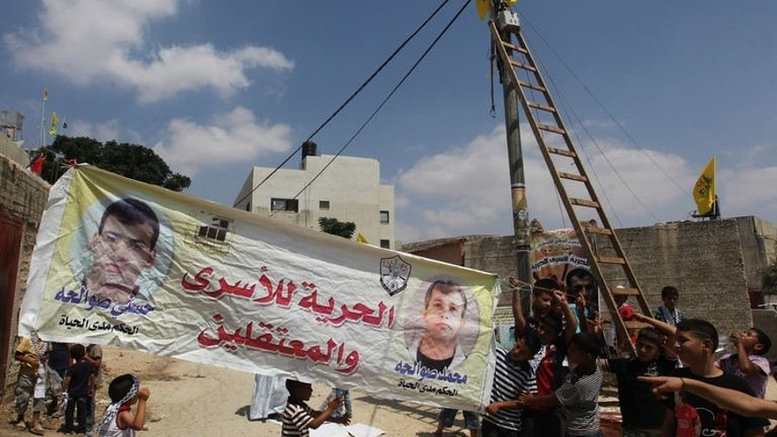 Relatives and friends of Palestinian prisoners raise a banner in the West Bank village of Azmut, east of the northern city of Nablus on August 12, 2013. Israel warned on Wednesday that it might shun a key EU research programme unless a compromise is found over the bloc's guidelines which bar funding to Jewish settlement entities.