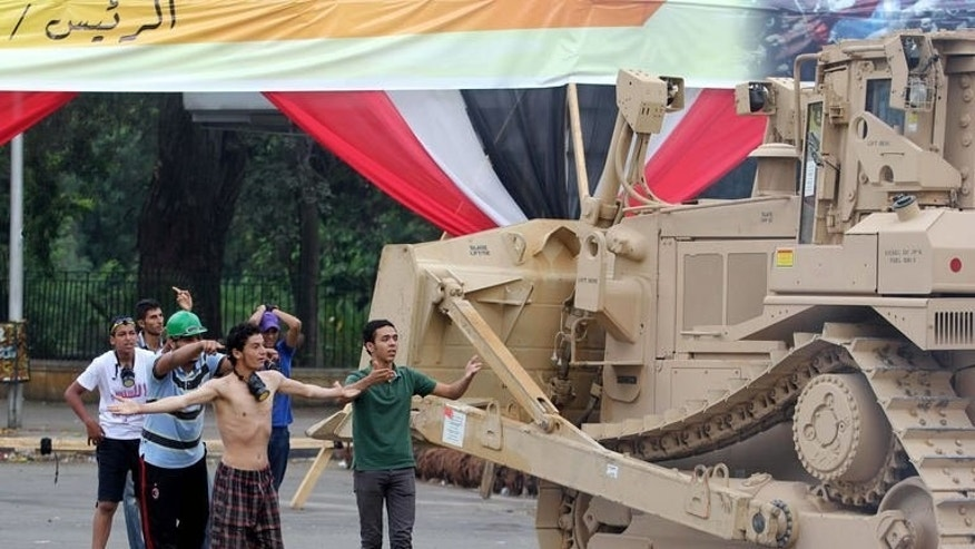 Demonstrators react as a military bulldozer moves in to disperse a protest camp on August 14, 2013 in Cairo. Jordan's opposition Islamists urged Egyptians to hold street protests to condemn Wednesday's deadly crackdown on demonstrators loyal to ousted president Mohamed Morsi, warning the Arab world's fate was at stake.