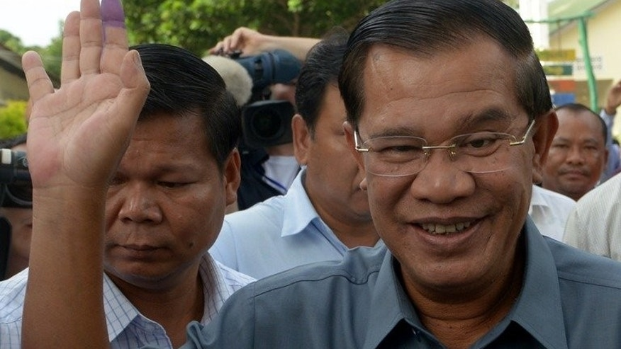 Cambodian Prime Minister Hun Sen (R) waves after casting his vote at a polling station in Kandal province on July 28, 2013. He is planning to attend an international entrepreneurship forum in Malaysia in October, organisers said Wednesday.