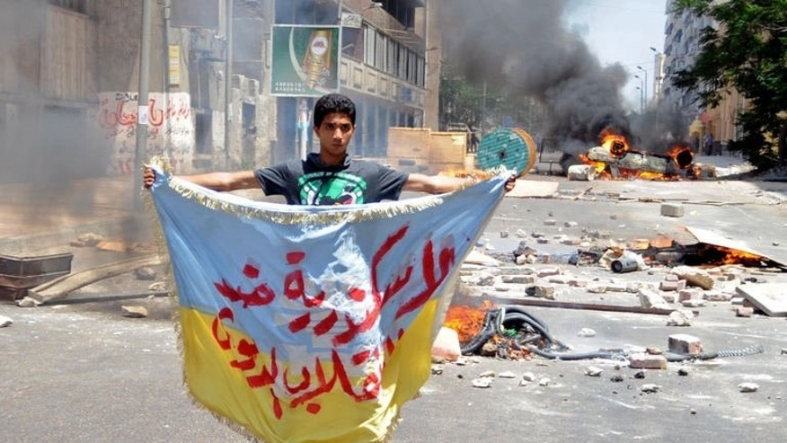 "A supporter of the Muslim Brotherhood and Egypt's ousted president Mohamed Morsi holds a banner reading in Arabic: ""Alexandria is against the coup"" as protestors set fire to a council building in Egypt's northern coastal city of Alexandria on August 14, 2013. Hundreds of angry supporters of ousted president Mohamed Morsi marched through Alexandria rioting and armed with wooden clubs."
