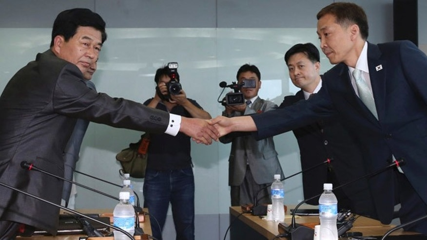 Aug. 14, 2013: Kim Kiwoong, right, the head of South Korea's working-level delegation, shakes hands with his North Korean counterpart Park Chol Su, left, before their meeting at Kaesong Industrial District Management Committee in Kaesong, North Korea.