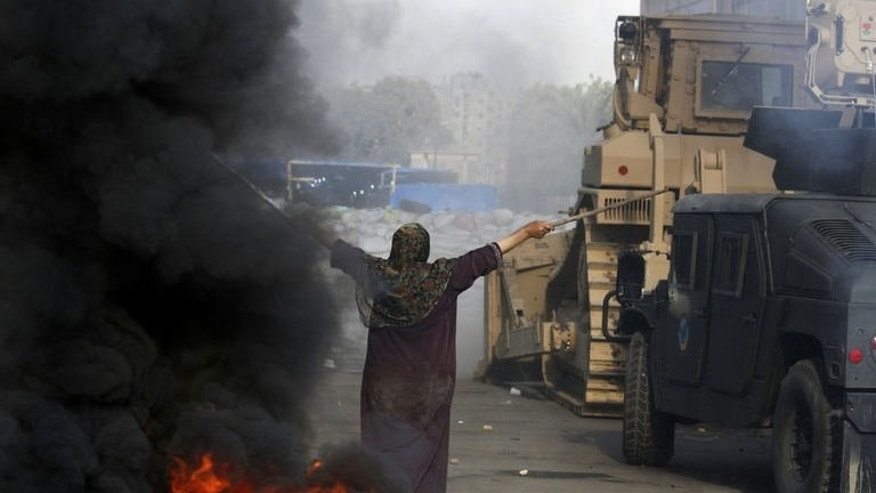 An Egyptian woman tries to stop a bulldozer during clashes that broke out as Egyptian security forces moved in to disperse supporters of deposed president Mohamed Morsi near the Rabaa al-Adawiya mosque in Cairo, on August 14, 2013. A TV cameraman for Britain's Sky News was shot and killed while covering the clashes in Egypt, the channel said.