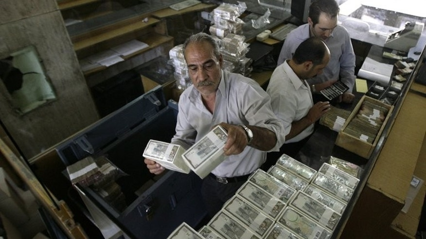 An employee stacks Syrian banknotes at the Syrian Central Bank in Damscus, on August 25, 2011. The central bank in war-torn Syria has lifted restrictions on the sale of dollars to individuals, in a bid to curb black market trade.