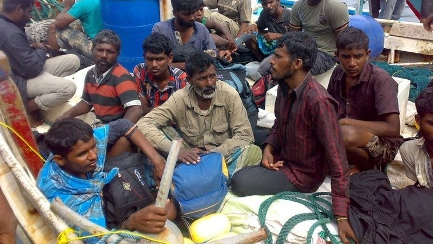 Sri Lankan asylum-seekers sit on their boat bound for Australia, picture on August 30, 2012. If elected Australia's opposition leader Tony Abbott plans to force arrivals seeking asylum to enter a work-for-welfare programme as part of a package of tough new measures.