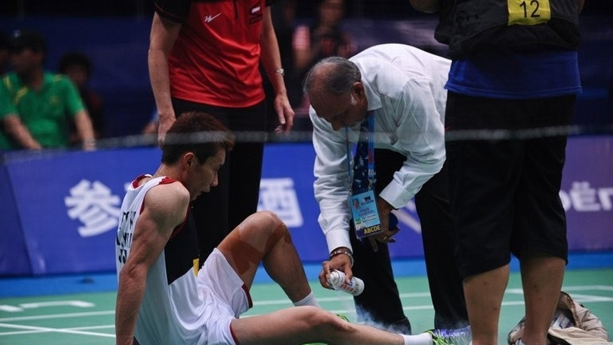 "Lee Chong Wei (C) receives medical treatment during his World Badminton Championships final against Lin Dan on August 11, 2013. ""It was so hot inside and Chong Wei was dehydrated. This led to him suffering cramps,"" Lee's coach Tey Seu Bock told The Star newspaper."