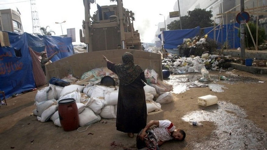 An Egyptian woman tries to stop a military bulldozer from hurting a wounded youth during clashes near Rabaa al-Adawiya mosque in eastern Cairo on August 14, 2013.