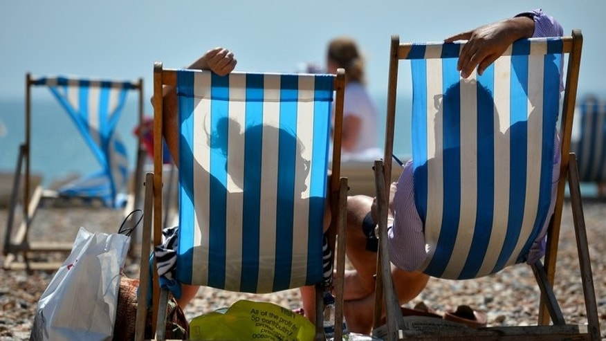People relaxe in deckchairs on the beach in Brighton, on the south coast during hot weather on August 1, 2013. Retail sales in Britain jumped 1.1 percent in July from the level in June as a heatwave fuelled spending on food, drinks and summer clothing, official data showed on Thursday.