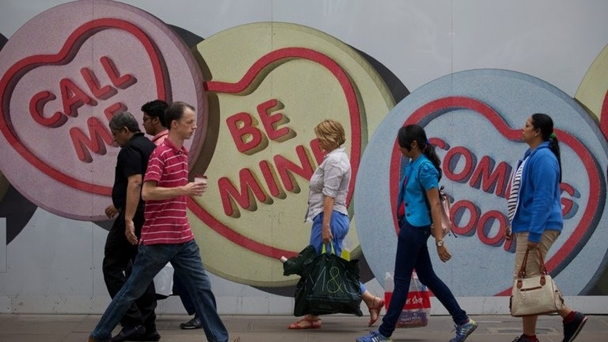 Shoppers walk past an advertising board for a new shop currently being re-fitted on Oxford Street in London on August 7, 2013. Britain's retail sales jumped 1.1 percent in July from the level in June as a heatwave fuelled spending on food, drinks and summer clothing, official data showed on Thursday