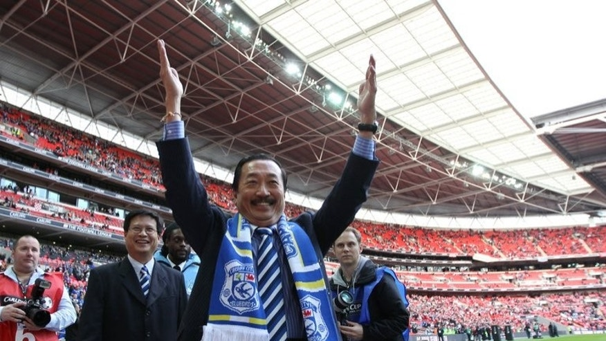 Cardiff City's Malaysian owner Vincent Tan (C) and Chairman Dato Chan Tien Ghee (2nd L) gesture to their team's fans before the start of the League Cup Final against Liverpool at Wembley Stadium in London, on February 26, 2012. Tan on Thursday admitted he hasn't ruled out changing the newly-promoted Premier League club's name.