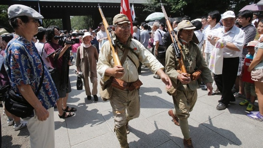 Aug. 15, 2013: Japanese men clad in outdated military costume march in to pay respects to the nation's war dead at the Yasukuni Shrine in Tokyo. Japan marked the 68th anniversary of its surrender in World War II with somber ceremonies Thursday and visits by senior politicians to the shrine honoring 2.5 million war dead that remains a galling reminder of colonial and wartime aggression.