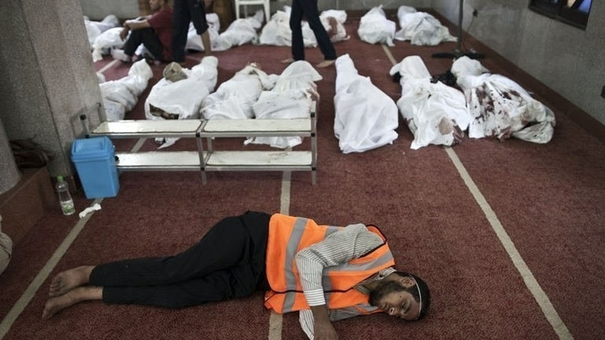 "A volunteer sleeps on the floor of a mosque in Cairo where lines of bodies wrapped in shrouds are laid out, on August 15, 2013. Egypt's Islamists called for a ""Friday of anger"" in Cairo after nearly 600 people were killed following a crackdown on their protest camps, as the UN urged ""maximum restraint"" from all sides."