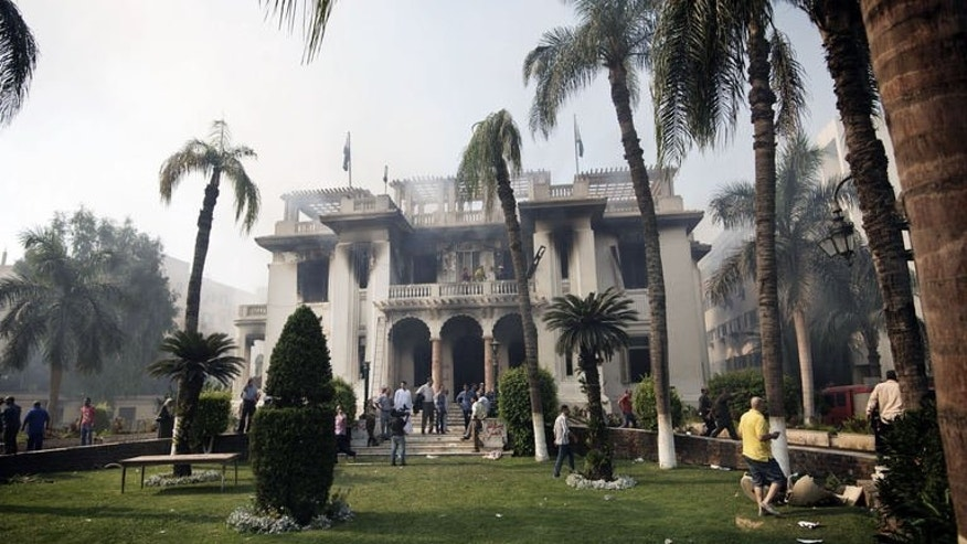 Bystanders, firefighters and workers stand by the Giza Governorate headquarters after it was, according to Egyptian State TV, torched by Islamists on August 15, 2013, in Cairo, Egypt. Private Egyptian television CBC showed footage of the headquarters in flames as men tried to douse the fire with hoses.