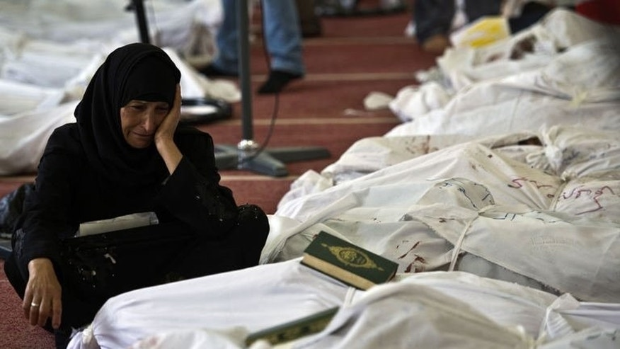 An Egyptian woman mourns over the body of her daughter wrapped in shrouds at a mosque in Cairo, on August 15, 2013. Egypt's Muslim Brotherhood has called for a march in Cairo, a day after bloody crackdown on its supporters who occupied protest camps demanding the reinstatement of president Mohamed Morsi.