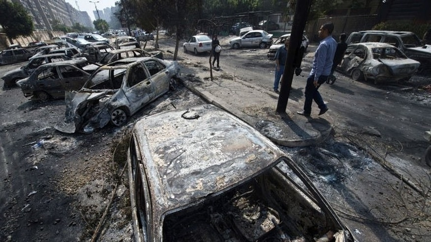 Egyptians pass by burnt vehicles outside the destroyed camp of ousted Mohammed Morsi supporters outside Rabaa al-Adawiya mosque on August 15, 2013 in Cairo, Egypt.
