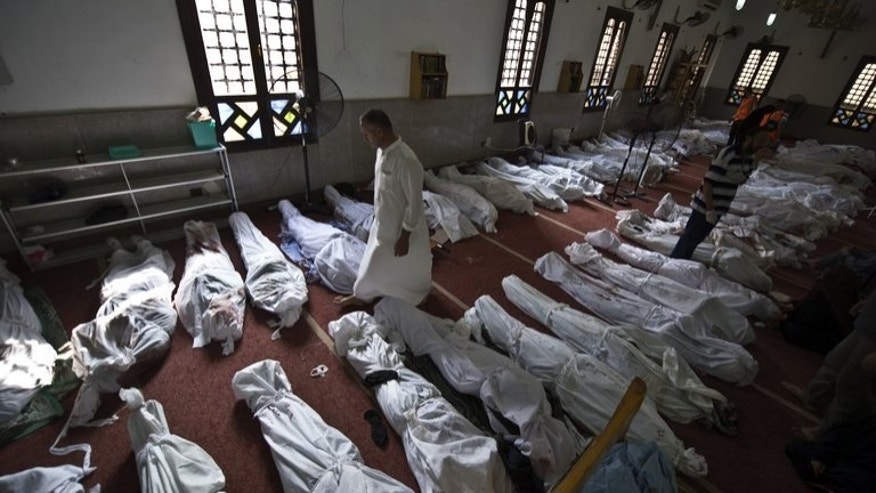 An Egyptian man walks between lines of bodies wrapped in shrouds at a mosque in Cairo on August 15, 2013. Egyptian police on Thursday entered a Cairo mosque containing the bodies of several dozen killed Islamist protesters after a brief standoff during which they fired tear gas, Islamist activists said.