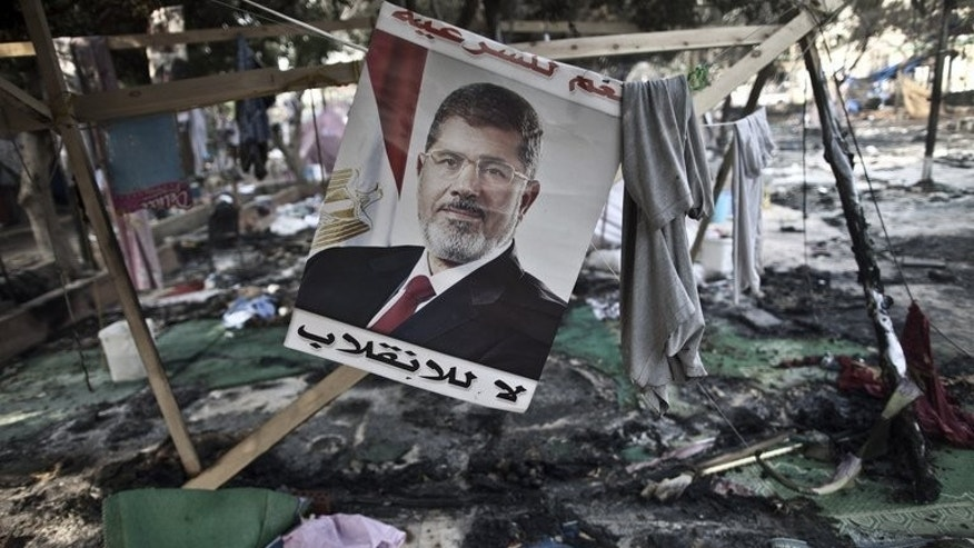 A picture of Egypt's ousted president Mohamed Morsi is seen hanging admist debris at Rabaa al-Adawiya Square in Cairo, on August 15, 2013. Supporters of Morsi have launched attacks on police posts in two provinces on Thursday, killing at least two policemen, according to security officials.