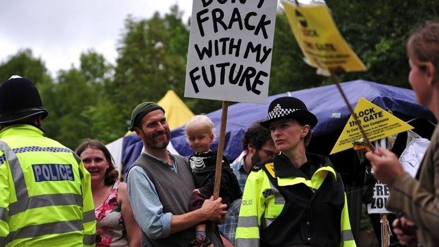 Police monitor protesters standing next to the entrance of a drill site operated by Cuadrilla Resources Ltd., in Balcombe, southern England, on July 31, 2013. Cuadrilla on Friday announced it was cutting back its activities at the site as over 1,000 protesters are preparing for a six-day 'action camp.'