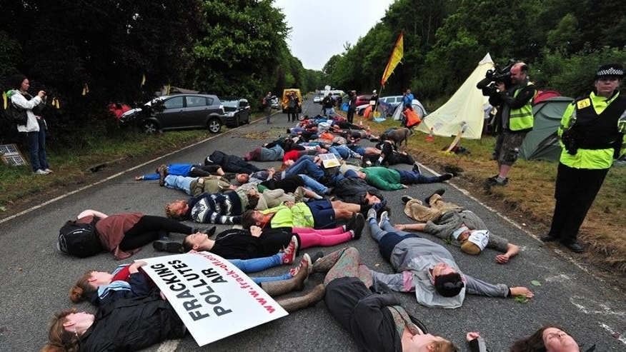 Protestors lie on the road leading to the entrance of a drill site operated by Cuadrilla Resources Ltd., in Balcombe, southern England, on July 31, 2013. Police so far have made around 40 arrests since the demonstrations began three weeks ago.