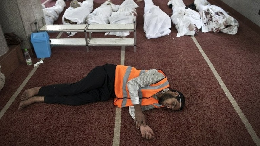 An Egyptian volunteer sleeps on the carpet of a mosque in Cairo where lines of bodies wrapped in shrouds were laid out on August 15, 2013, following a bloody crackdown on the protest camps of supporters of ousted Islamist president Mohamed Morsi the previous day.