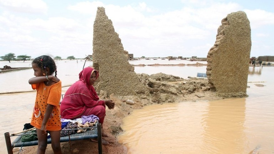 A woman sits next to her house in a flooded street on the outskirts of Khartoum last week. Two weeks after the worst flooding in years hit Sudan's capital region, killing about 30 and affecting more than 84,000, ankle-deep muddy water still covers this district east of the Blue Nile river.