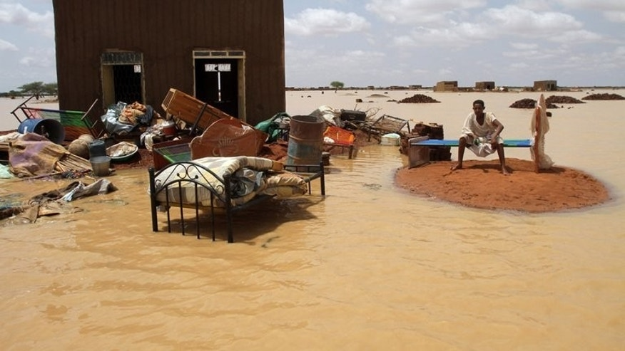 A man sits next to his house in a flooded street on the outskirts of Khartoum on last week. Heavy roofs have collapsed in on themselves, crushing what was below, while the bricks in less sturdy homes have simply tumbled down, forming piles of rubble.
