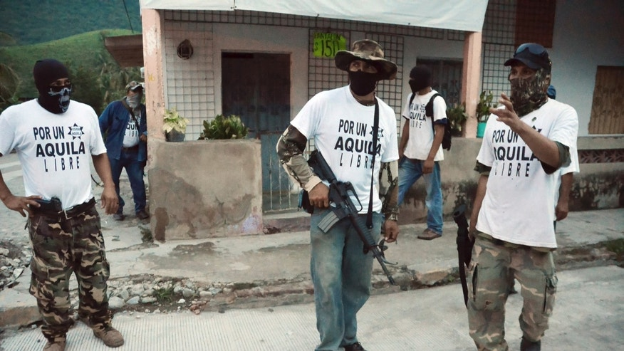 Armed members of a local self-defense group stand at a street corner in the town of Aquila, Mexico, early Wednesday, July 24, 2013.