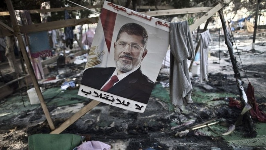 A picture of Egypt's ousted president Mohamed Morsi is seen hanging admist debris at Rabaa al-Adawiya sqaure in Cairo on August 15, 2013, following a crackdown on the protest camps the previous day.