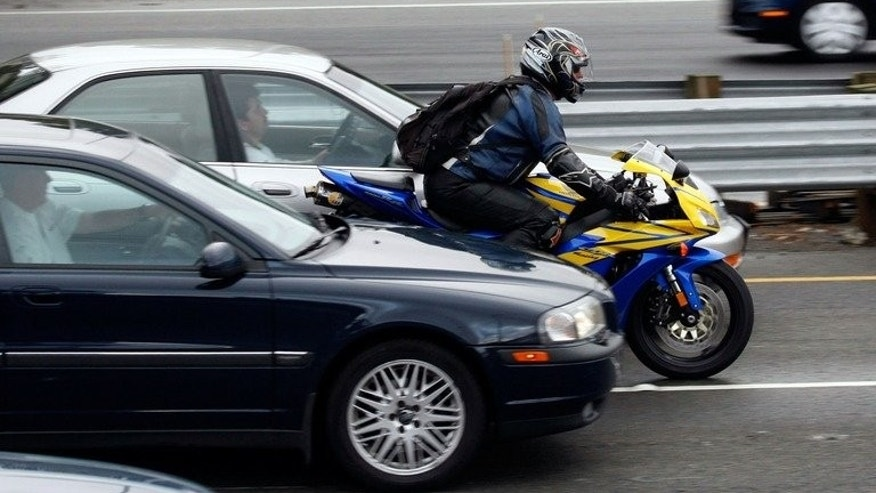 A motorcyclist rides between cars in slow moving traffic on Highway 101 on 16 October 2007 in Corte Madera, California. A Canadian man faces several charges and Can$1,200 in fines after speeding past police with a video camera on his motorcycle that recorded his bad driving, authorities said Thursday.