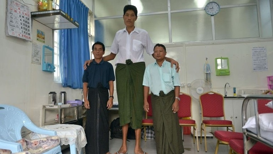 Win Zaw Oo, Myanmar's tallest man, pictured with his cousins at a Yangon hospital on July 10, 2013. At seven foot eight inches he is believed to be the country's tallest man, and a recent rise to fame means he can finally seek treatment abroad for the health condition behind his towering height.