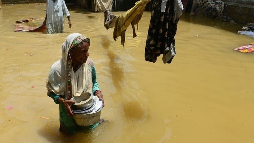A Pakistani woman walks through floodwaters following heavy monsoon rain in Karachi, on August 5, 2013. Pakistan officials say floods triggered by monsoon rains have killed 96 people in the past two weeks and affected nearly 90,000 others.