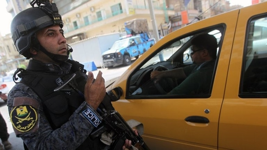 An Iraqi policeman controls a checkpoint on July 23, 2013 in Baghdad. A series of bombings struck Baghdad on Thursday, killing at least 16 people, officials said, a day after Iraqi Prime Minister Nuri al-Maliki vowed to press a campaign against militants.