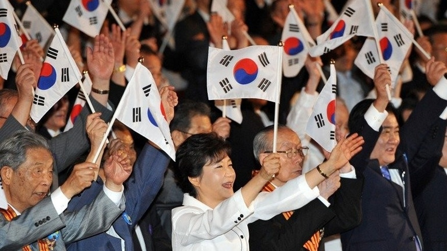 South Korea's President Park Geun-Hye (C) gives three cheers for the country during a ceremony marking the 68th anniversary of the liberation from Japan's 1910-45 colonial rule, in Seoul, on August 15, 2013. Park proposed a family reunion event with the North a day after the two nations agreed on reopening a shuttered joint industrial zone in a sign of easing of tensions.