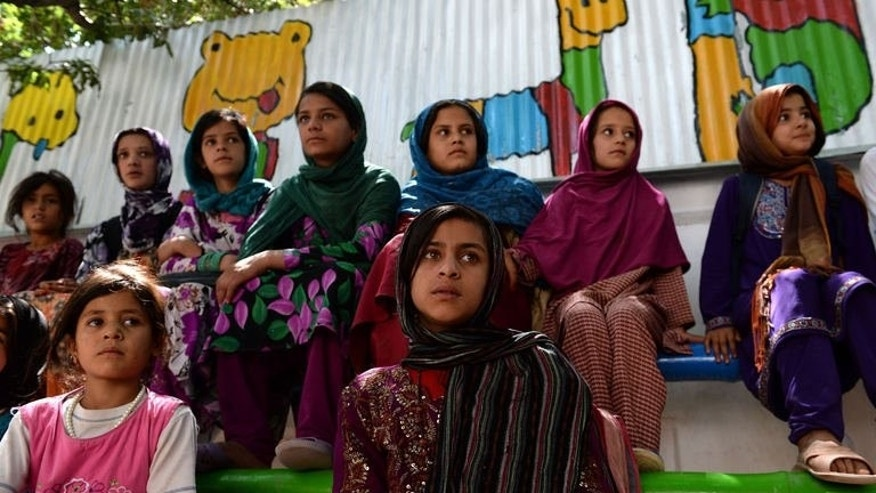 Girls watch a performance during the 8th Afghanistan Juggling Championships, in Kabul, on August 14, 2013. The event is part of Kabul's week-long circus festival, which includes street parades and coaching sessions in refugee camps.