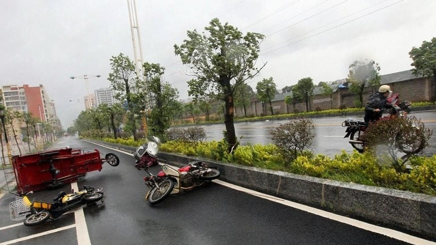 Vehicles are blown onto the ground by strong wind as Typhoon Utor lands in Yangjiang, China's Guangdong province, on August 14, 2013. The confirmed death toll from Typhoon Utor has risen to eight in the Philippines as the storm swept across southern China, where thousands had fled its path.