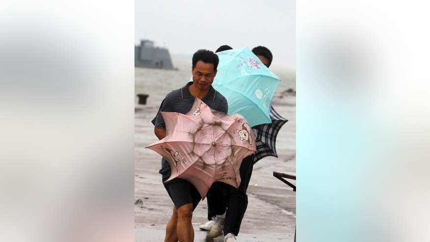 People walk into a strong wind after Typhoon Utor landed in Yangjiang, south China's Guangdong province, on August 14, 2013. The confirmed death toll from Typhoon Utor has risen to eight in the Philippines as the storm swept across southern China, where thousands had fled its path.
