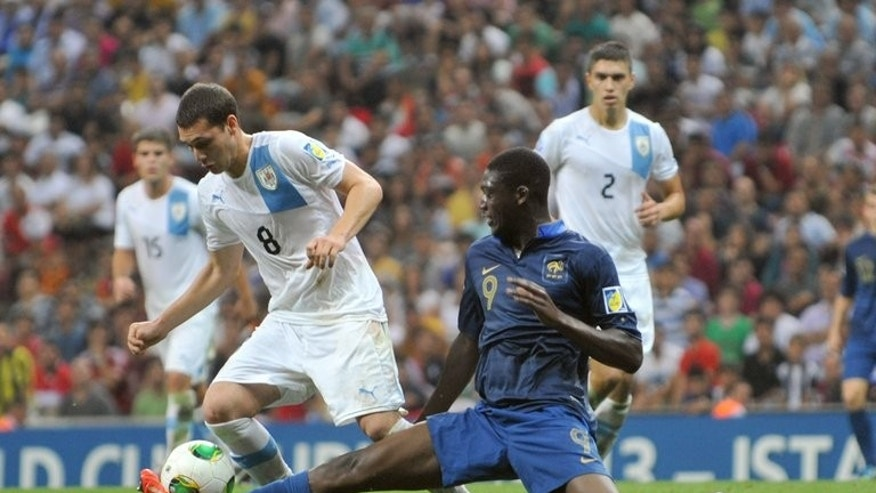 French forward Yaya Sanogo (right) and Uruguay's Sebastian Cristoforo on July 13, 2013 during the FIFA Under 20 World Cup final football match in Istanbul. Sanogo is Arsenal manager Arsene Wenger's only confirmed signing of the transfer window so far.