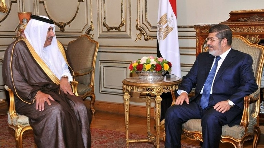 Mohamed Morsi (right) meets Qatari Premier Sheikh Hamad bin Jassem al-Thani in Cairo on April 30. Only Qatar, a Brotherhood patron, and Tunisia, whose ruling Ennahda party is affiliated with the the movement, strongly condemned Wednesday's assault on Morsi supporters.