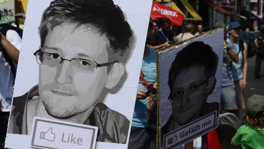 "Demonstrators hold placards featuring an image of former US intelligence contractor Edward Snowden, Berlin, July 27, 2013. WikiLeaks founder Julian Assange has denied speculation that US intelligence leaker Snowden was interrogated by Russian authorities, telling Australian media they had ""behaved well""."