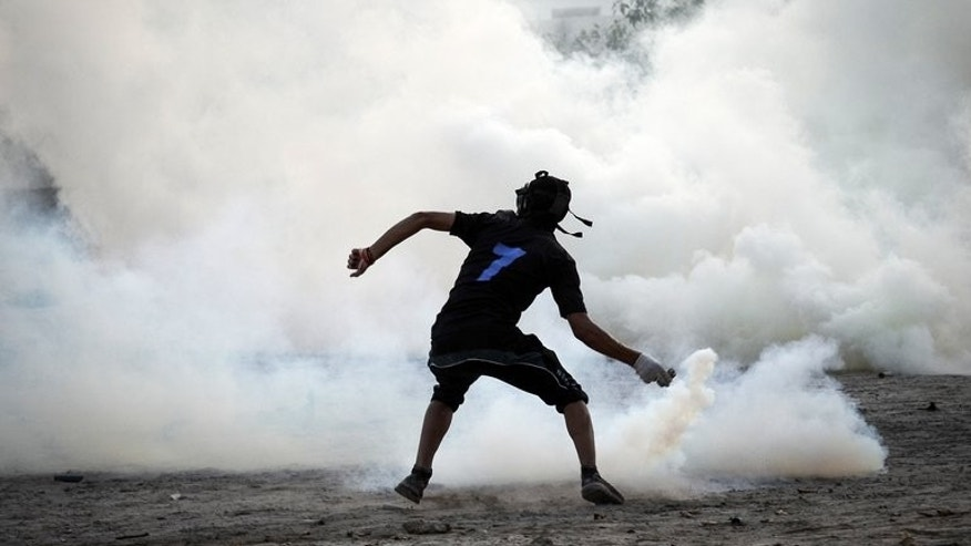 A protestor throws back a tear gas canister at a protest in Abu Saiba, west of Manama, on Thursday. Protesters calling for the overthrow of Bahrain's ruling Sunni monarchy clashed with police across several Shiite villages overnight, witnesses said Friday without reporting casualties.