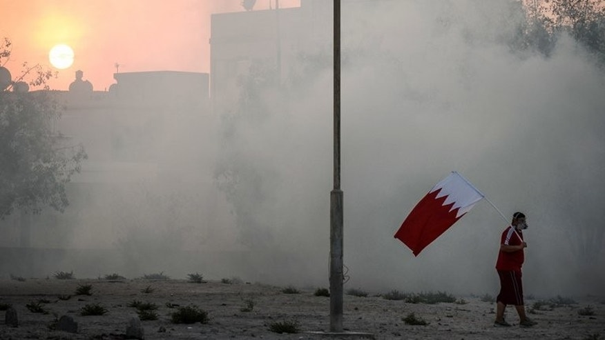 A protester holds the national flag at a rally in Abu Saiba, west of Manama, on Thursday. Protesters calling for the overthrow of Bahrain's ruling Sunni monarchy clashed with police across several Shiite villages overnight, witnesses said Friday without reporting casualties.
