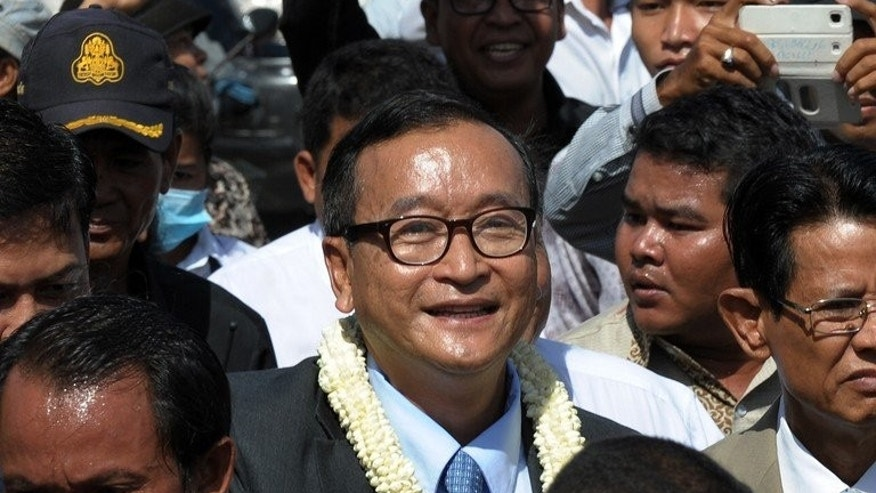 Sam Rainsy (C), leader of the opposition Cambodia National Rescue Party on a street in Phnom Penh on August 16, 2013. Rainsy said mass protests over disputed election results would be a 'last resort'