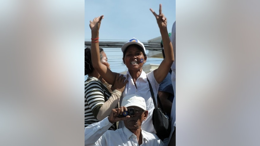 A supporter of the opposition Cambodia National Rescue Party gestures in Phnom Penh on August 16, 2013, as Sam Rainsy, leader of the opposition Cambodia National Rescue Party (CNRP), greets supporters following his return from the US to attend his daughter's wedding.