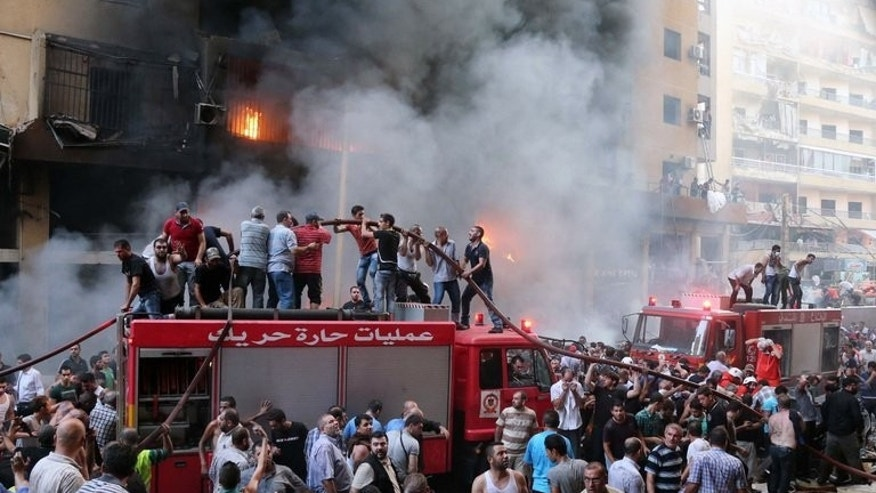 People help rescue workers put out fires after a car bomb in Beirut's southern suburbs on Thursday. Lebanon was holding a day of mourning Friday after a car bombing killed at least 22 people in a Beirut stronghold of Shiite group Hezbollah which backs Syria's embattled president.