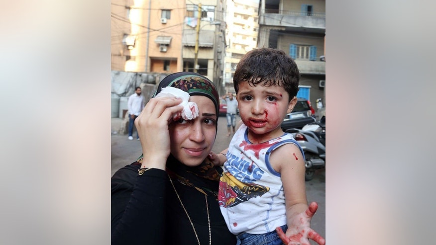 A boy and his mother are seen at the site of a car bomb blast between the Bir el-Abed and Roueiss neighbourhoods, in the southern suburbs of Beirut, on August 15, 2013. The Lebanese Red Cross said at least 18 people were killed and 245 others wounded in the attack.